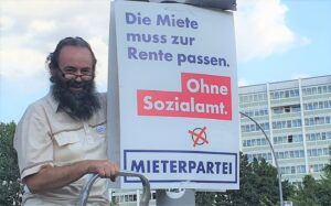 """Thomas hängt Wahlplakat """"Die Miete muss zur Rente passen. Ohne Sozialamt. MIETERPARTEI"""""""